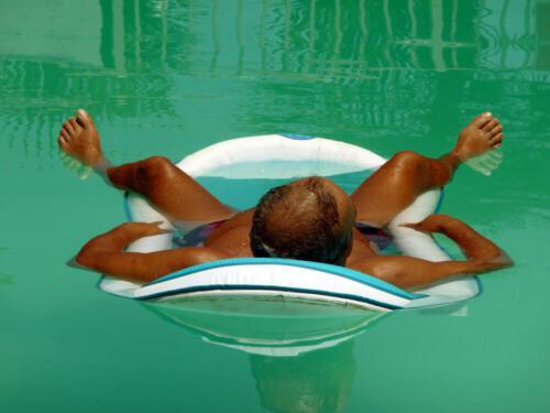 Mann schläft auf Luftmatraze im Pool